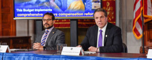 cuomo at desk at a conference with another speaker to his rigiht