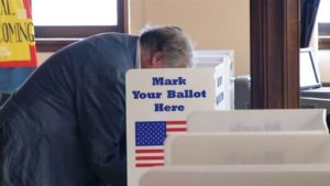 Man voting in voting booth with an American flag and