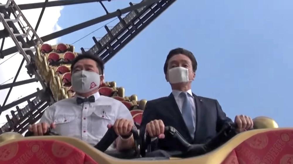 two men on a roller coaster wearing masks