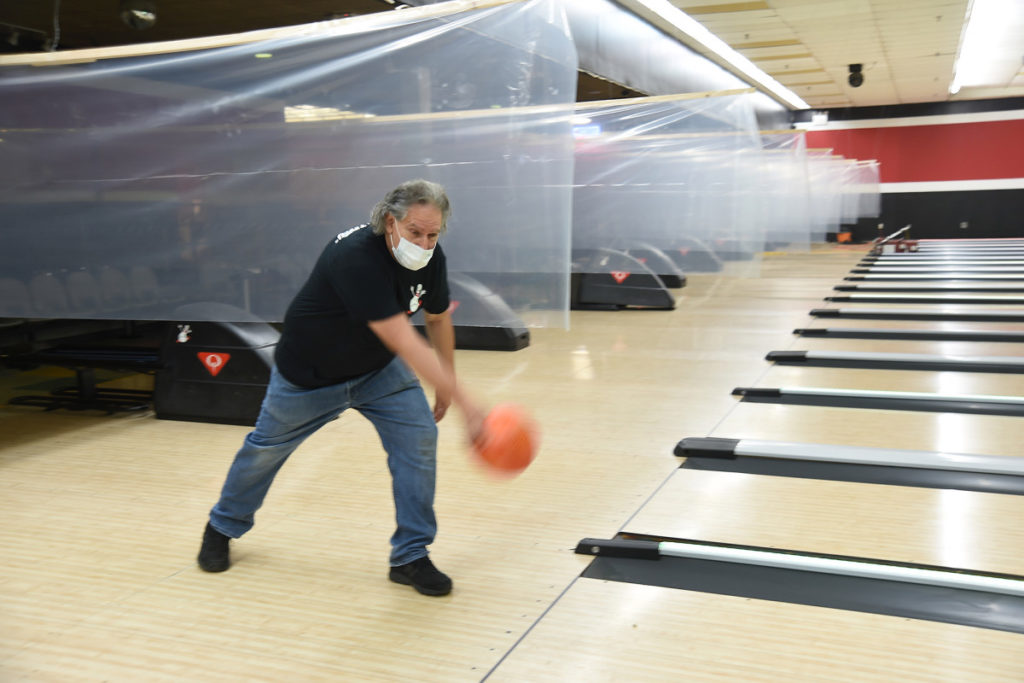 Man bowling with mask on